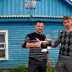 due giovani brinadano con della birra nel villaggio di Listvianka sulle rive del lago baikal , asia, russia, siberia, |two young men toasting with beer in the village of Listvyanka,lake baikal, asia, russia, siberia