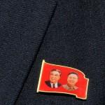 corea del nord, la spilla sulla giacca di un agente della sicuezza con l'effige dei presidenti coreani Kim Jong, padre deceduto ed il successore figlio Kim Jong-Un