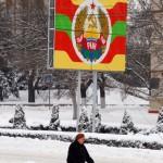 Transnistria una donna anziana si incammina tra la neve. Sullo sfondo la bandiera della Transnistria Ph © Nicola De Marinis