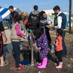 profughi riempiono bottiglie d'acqua ad un rubinetto nel campo allestito nelle campagne di idomeni in grecia