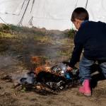 un bambino brucia una bottiglia di plastica nel campo profughi a idomeni in grecia