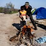 un padre con suo figlio accendono il fuoco nel campo profughi di idomeni sul confine tra grecia e macedonia