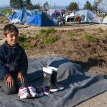 un bambino vende stivali di gomma nel campo profughi a idomeni in grecia
