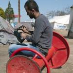 un profugo afgano lucida le scarpe nel campo profughi allestito nell'areadi servizio eko sulla strada per idomeni in grecia