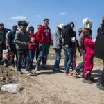 profughi in fila per una bottiglia d'aacqua nel campo allestito a Idomeni tra grecia e macedonia
