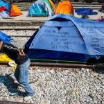 un profugo fa il segno di vittoria tra le tende nellla stazione di Idomeni confine tra grecia e macedonia