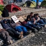 profughi sdraiati sui binari della stazione di idomeni in grecia