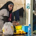 donna siriana pela delle patate nel campo profughi allestito nella stazione di idomeni in grecia