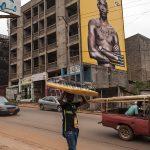 un giovane venditore ambulante di occhilali da sole in una via di Yaounde in camerun