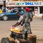 un venditore ambulante di ananas e anguria in una via di yaoundè in camerun