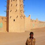 Niger,ragazzino davanti al minareto di Arlit