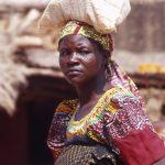 Burkina Faso, donna che trasporta un sacco di miglio sulla testa