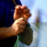Croazia isola di Pag, un pescatore rammenda la rete da pesca