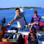 Croazia isola di Pag , giovani pescatori vendono il pesce appena pescato sul molo di Novalja