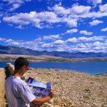 Croazia isola di Pag, un turista osserva la mappa dell'isola nel tipico paesaggio mediterraneo