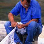 Croazia, isola di Pag, un pescatore rammenda la rete da pesca sul molo a Mandre