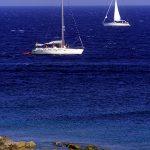 Dalamazia, Isola di Korkula, due barche a vela navigano davanti alla costa di Brna