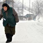 Romania, una donna anziana cammina lungo la strada innevata per raggiungere il paese di Scheia