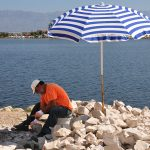 croatia, island of nin, a man at work splitting stones for the construction of walls, well-known in much of croatia