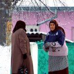 Romania, donne anziane davanti ad una abitazione in un villaggio rurale in pieno inverno nella Romania dell'est