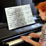 eurasia, georgia, una donna anziana suona al pianoforte nel centro dei profughi