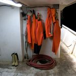 Europe, Croatia, water resistant over suit working on board a vessel