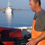 Europe, Croatia, Island of Pag, Novalja port, a fisherman on board at the tapes prepared with fish caught at night