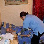 Georgia, un'assistente sociale della caritas georgia, presta delle cure ad un anziano profugo nella sua casa a Gori